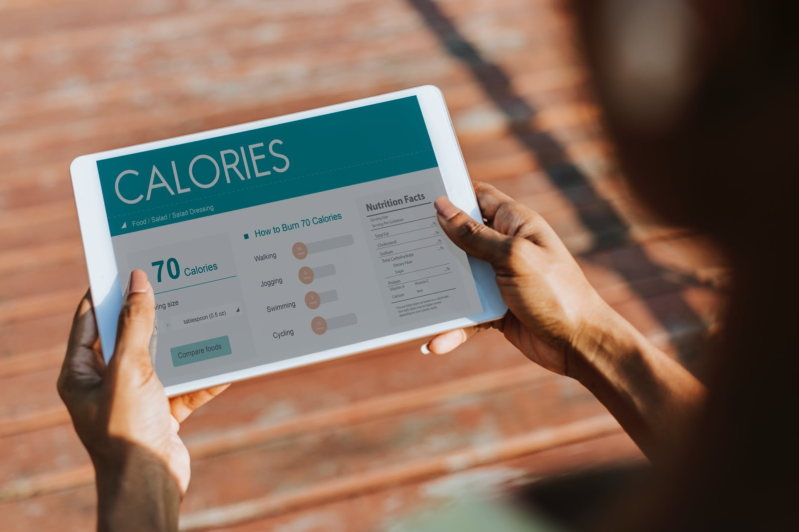 500-calorie meals: Hands hold a tablet that's open to a calorie tracker