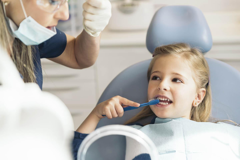 Child brushing teeth at dentist