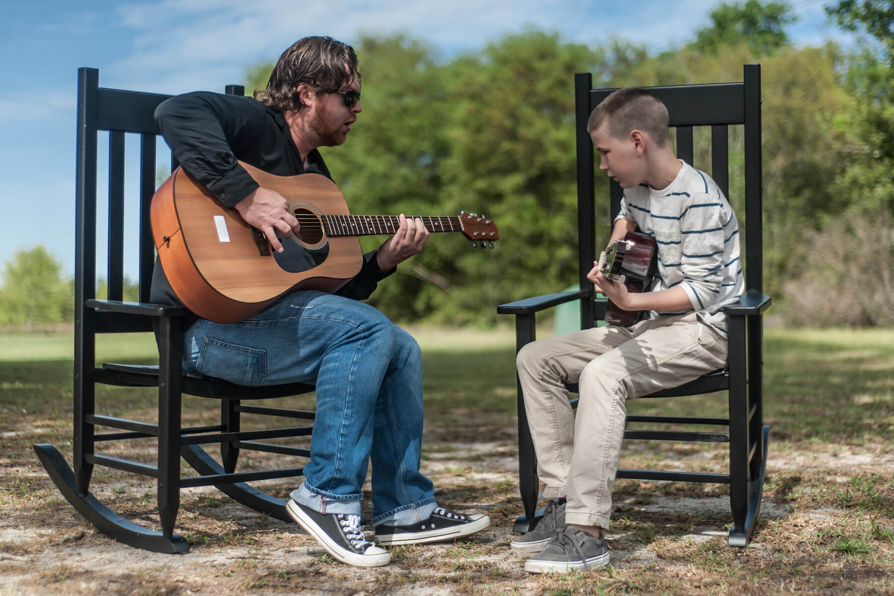 Student and instructor having a guitar lesson outdoors.