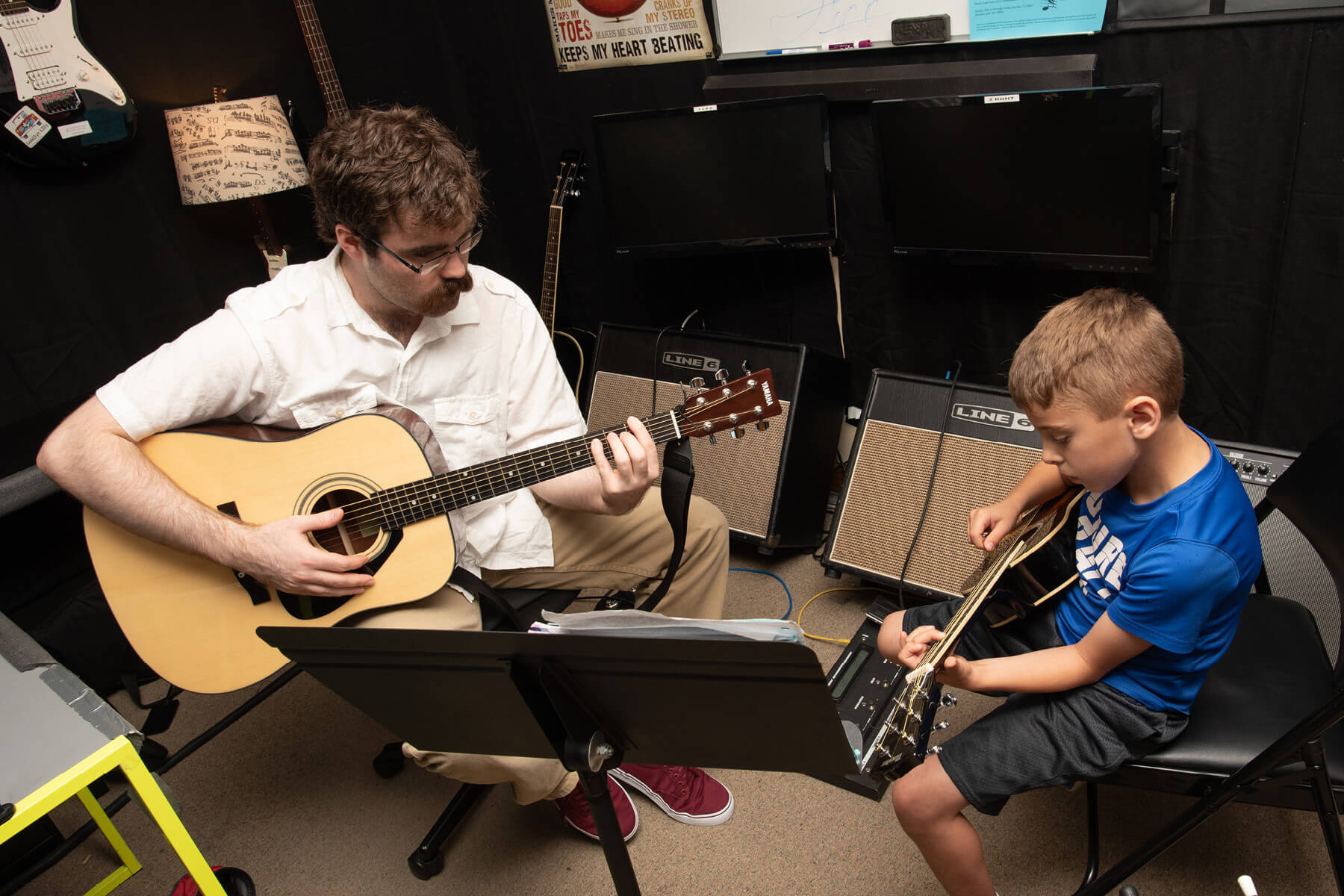 Instructor and student playing acoustic guitar in room with Line 6 amps.