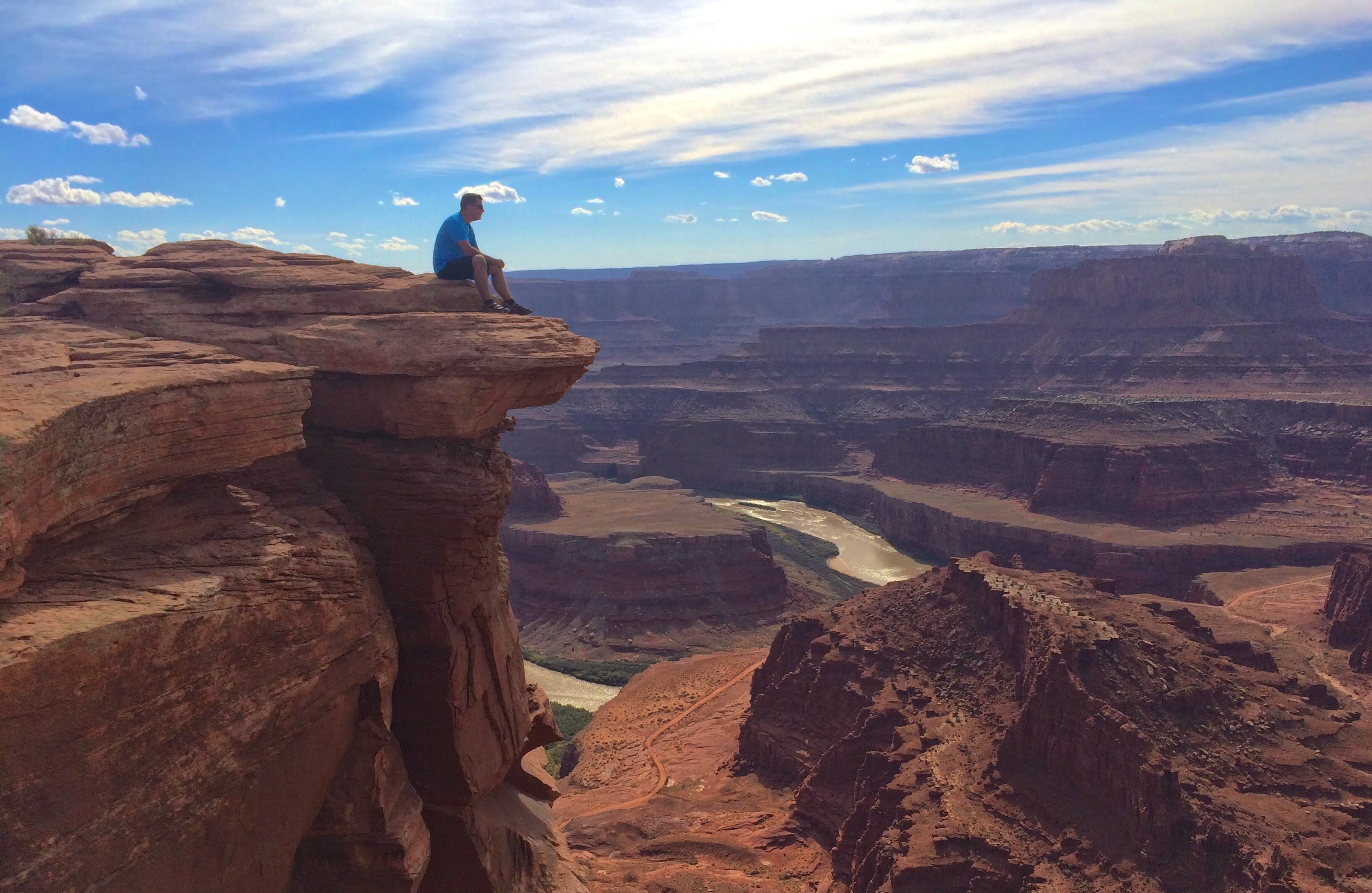 Person sitting on edge of cliff overlooking Utah mountains