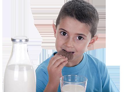young boy enjoying milk and cookies