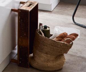 Tasche mit Einkäufen und rustikalem Holzkasten in Landhausküche