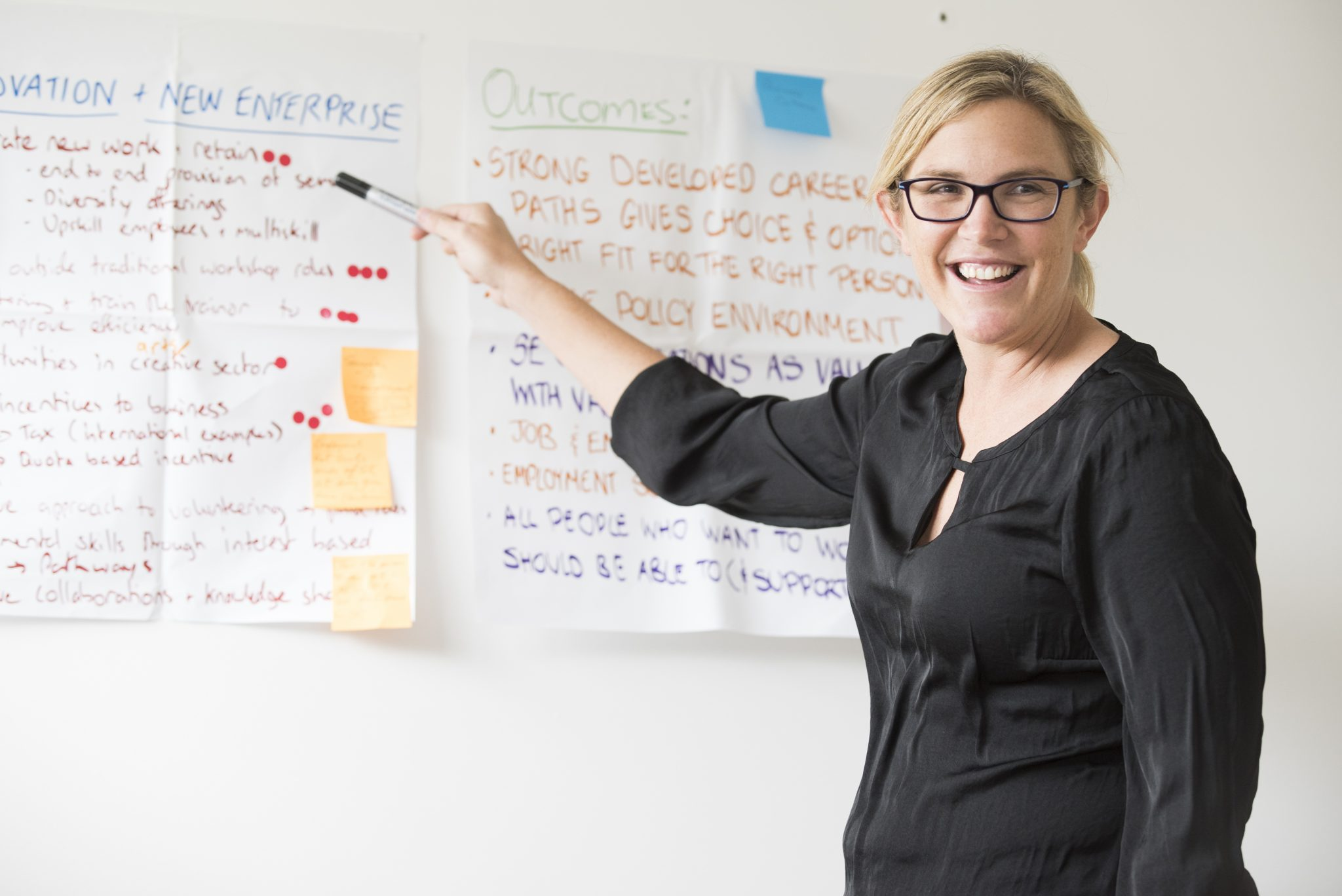 A photo of a woman facilitating a workshop. She is pointing to post-it notes on the wall behind her.