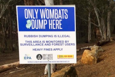"Photo of a sign saying ""Only wombats dump here"" in the forest."
