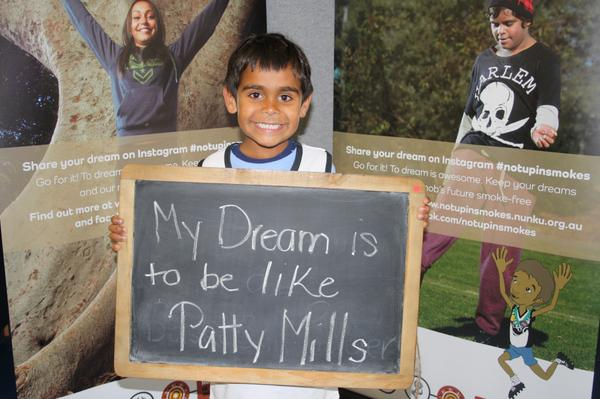 "Photo of a young Aboriginal boy holding a chalk board on which he has written My dream is to be like Patty Mills""."