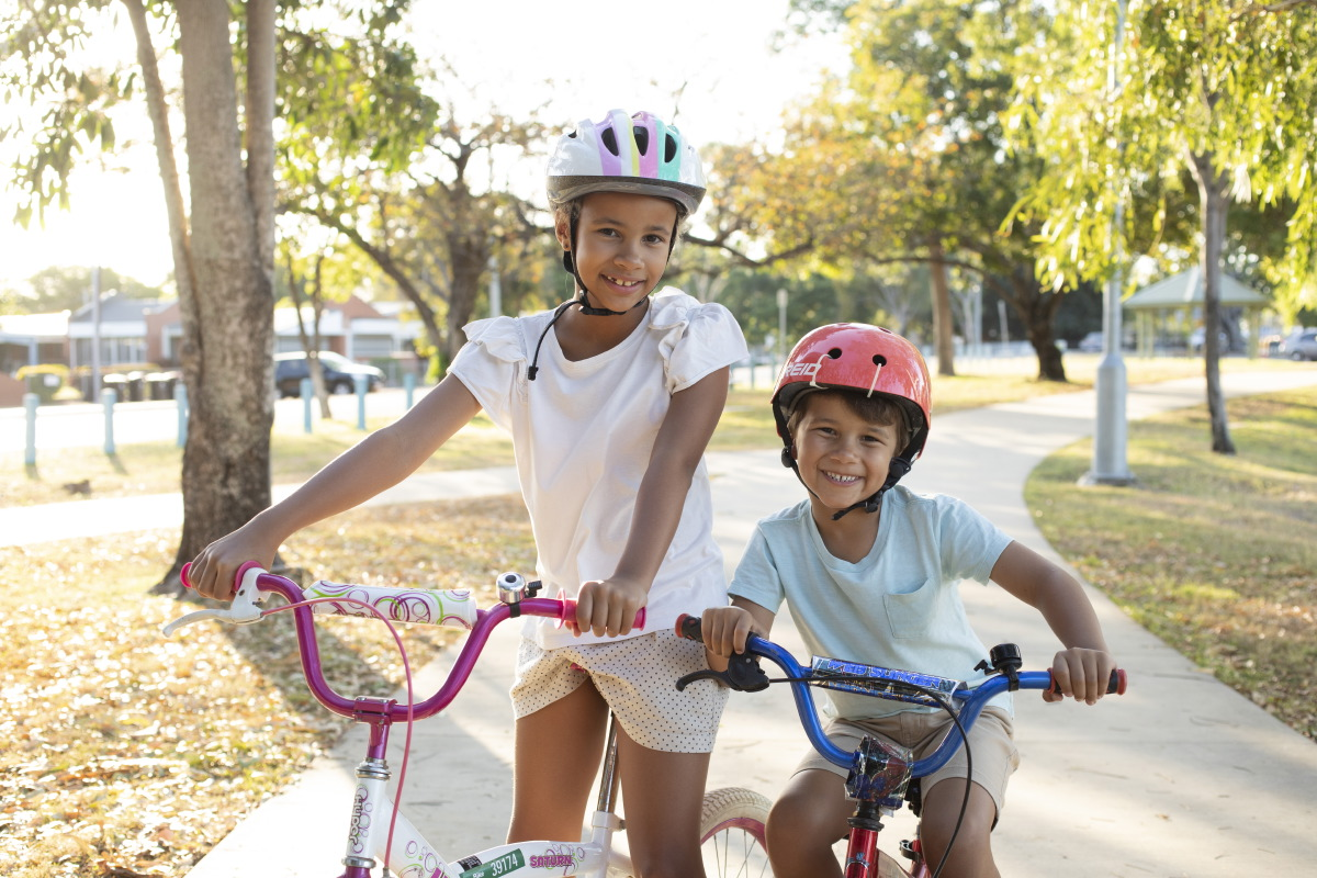 Photo of a girl and a boy riding their bikes.