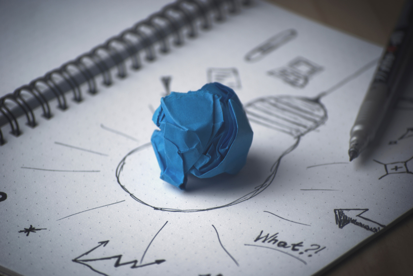 Photo of a book with a drawing of lightbulb on the page with various sketches and charts around it. In the middle of the bulb is a scrunched up piece of blue paper.