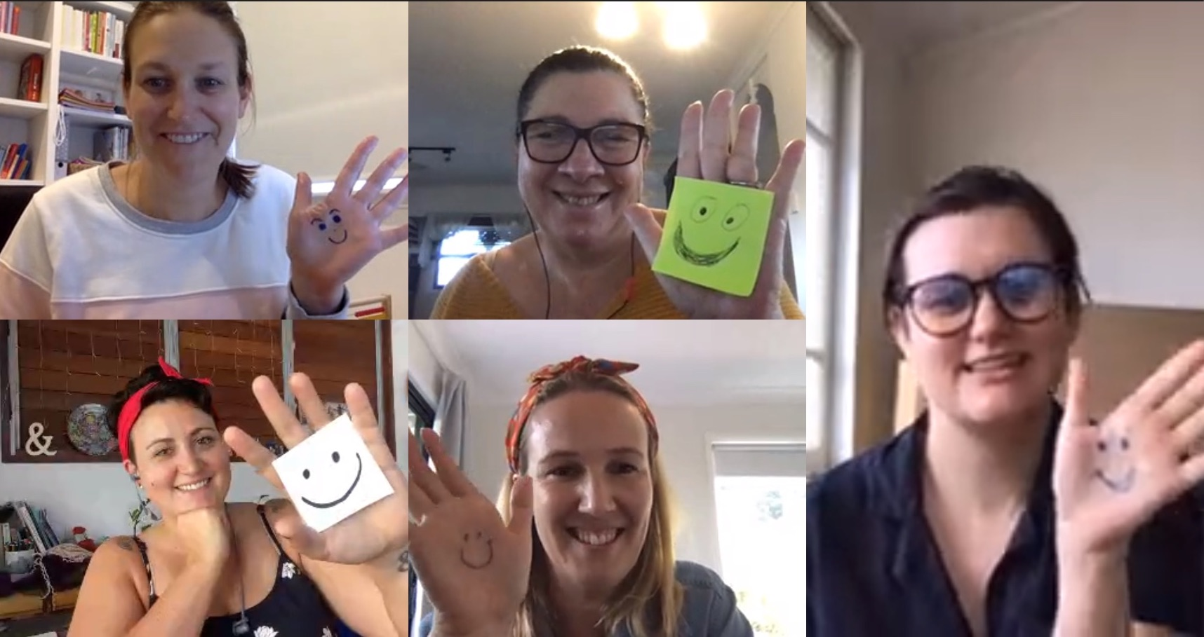 Members of The Social Deck team waving at the camera with smiley faces drawn on their hands for National Volunteer Week.