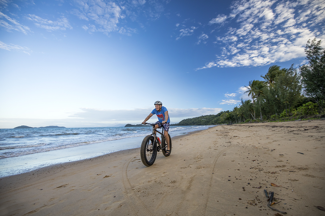 Photo of a man riding a bike along a beach with water and trees in the background.
