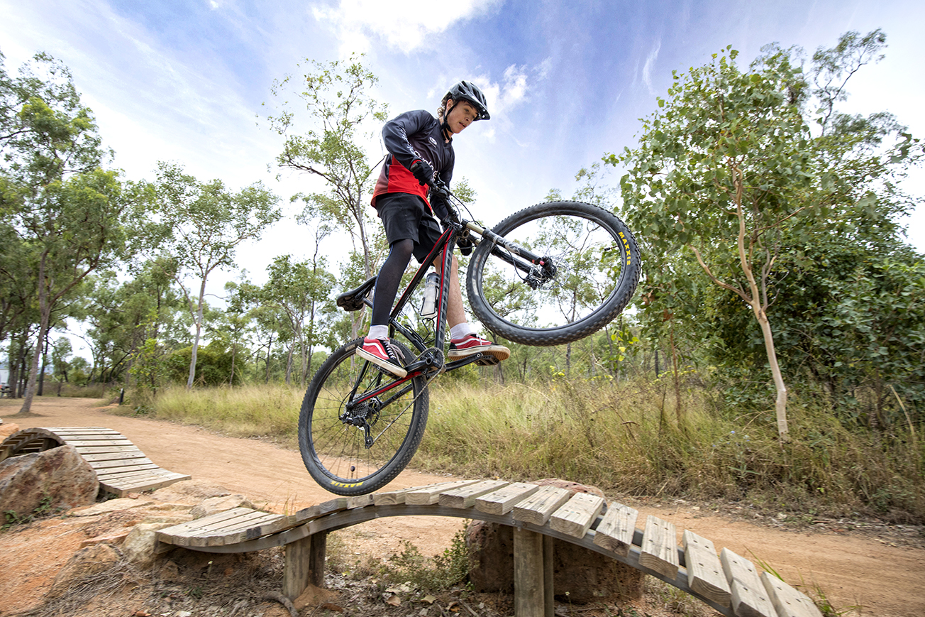 Photo of a boy on a mountain bike riding over a bike jump.