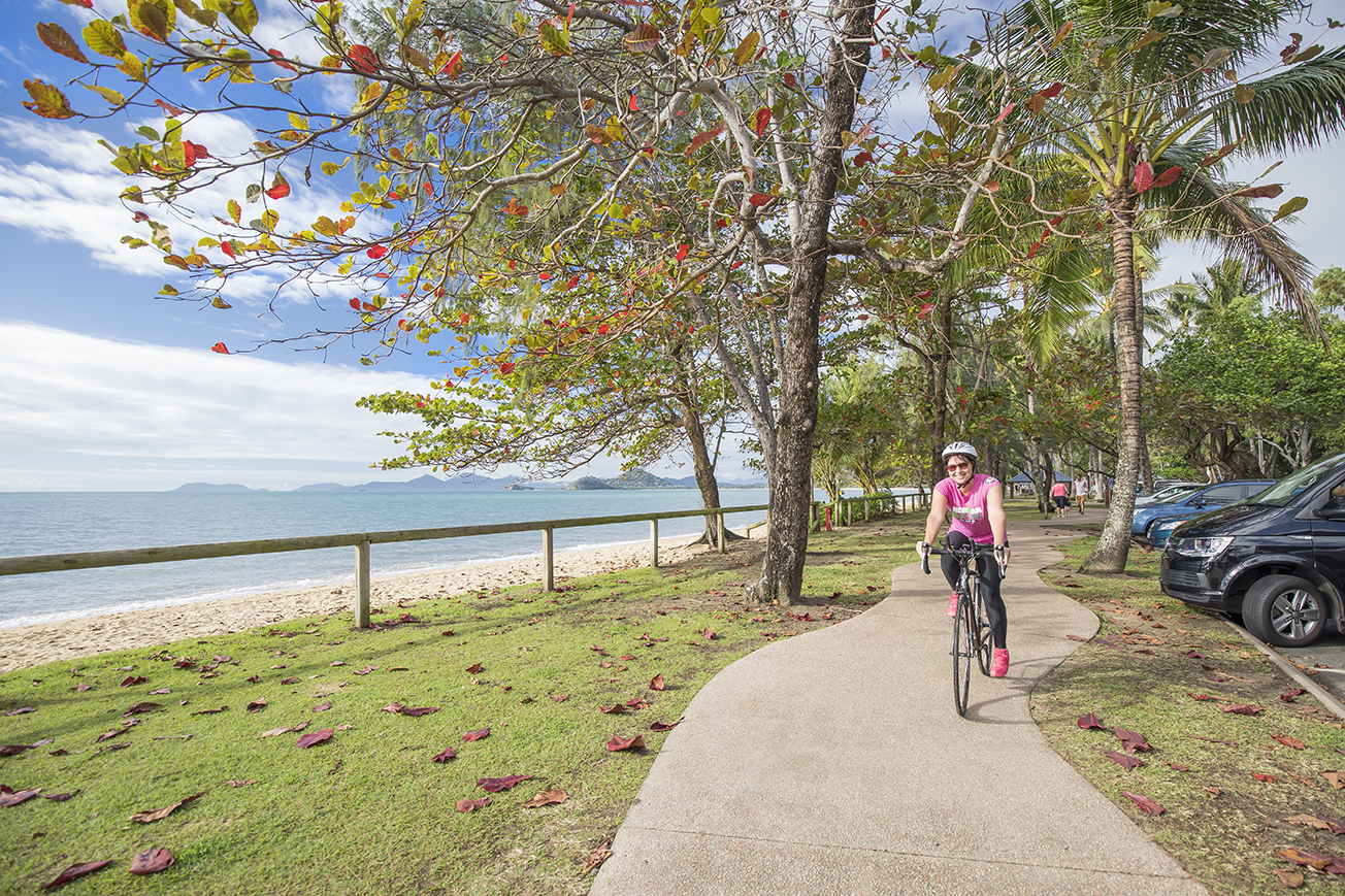 Photo of a woman riding a bike on a bike path with the ocean and trees in the background.