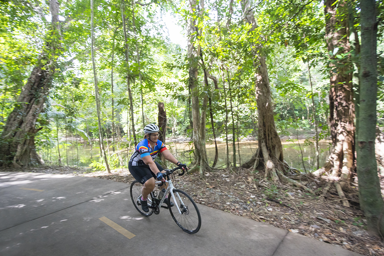 Photo of a woman riding a bike through rainforest with water in the distance.