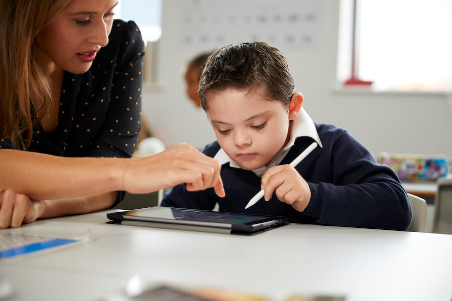 Student with down syndrome using an ipad with assistance from a female teacher
