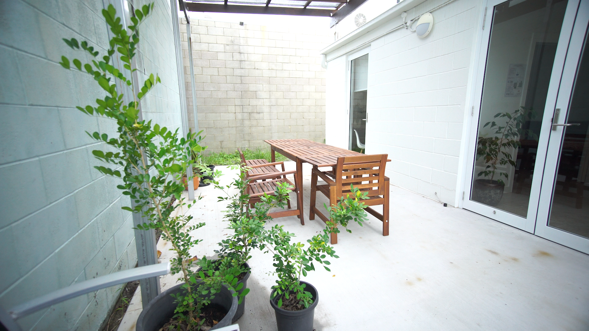 An outdoor brick courtyard with a brown wooden outdoor setting and green plants