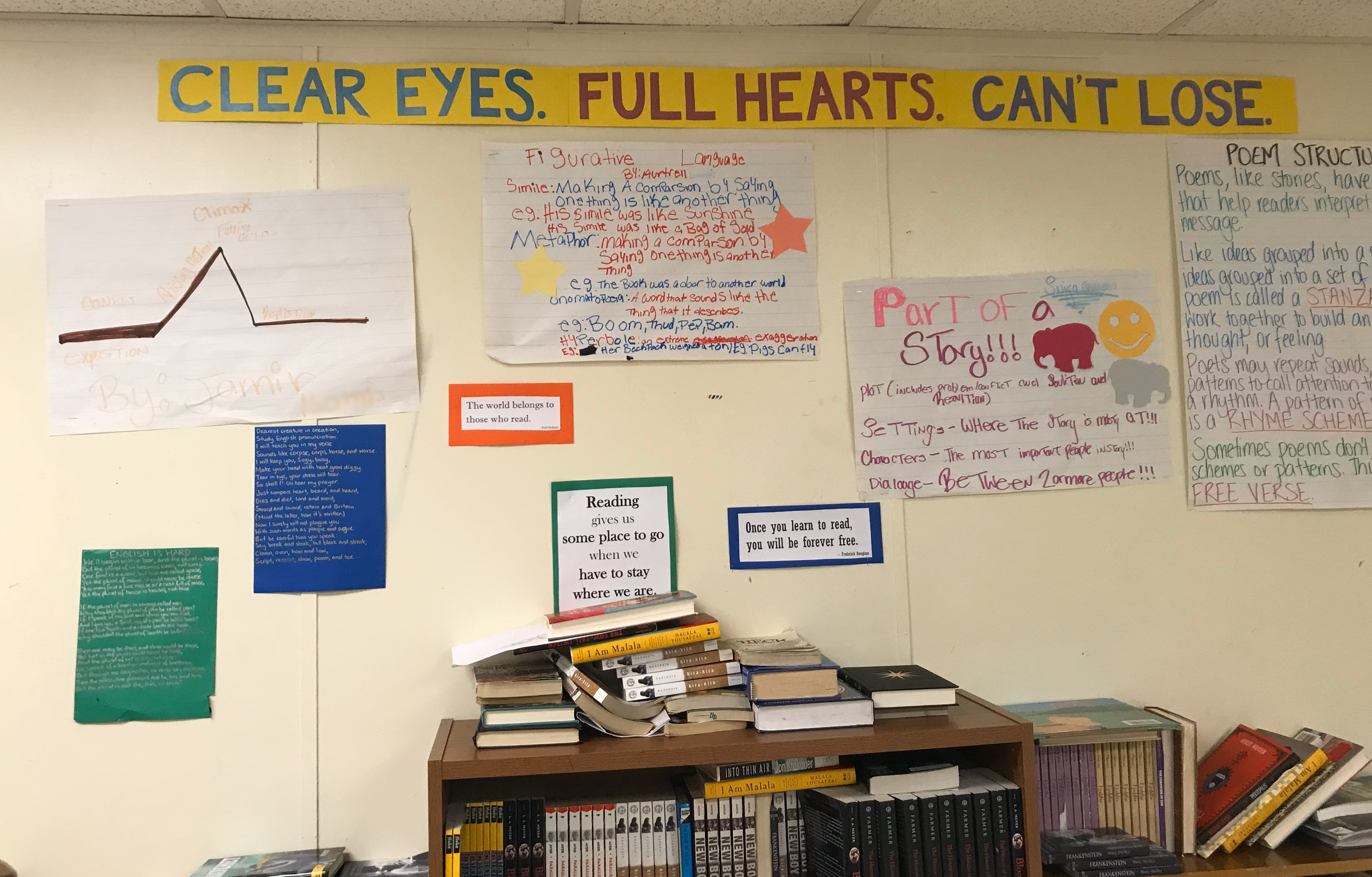 """Wall covered in handmade posters. Banner at the top says """"CLEAR EYES. FULL HEARTS. CAN'T LOSE."""". Headings on posters say """"Figurative Language"""", """"Part of a story"""" and """"POEM STRUCTURE"""". Below the posters are the tops of some bookshelves, covered in piles of books."""