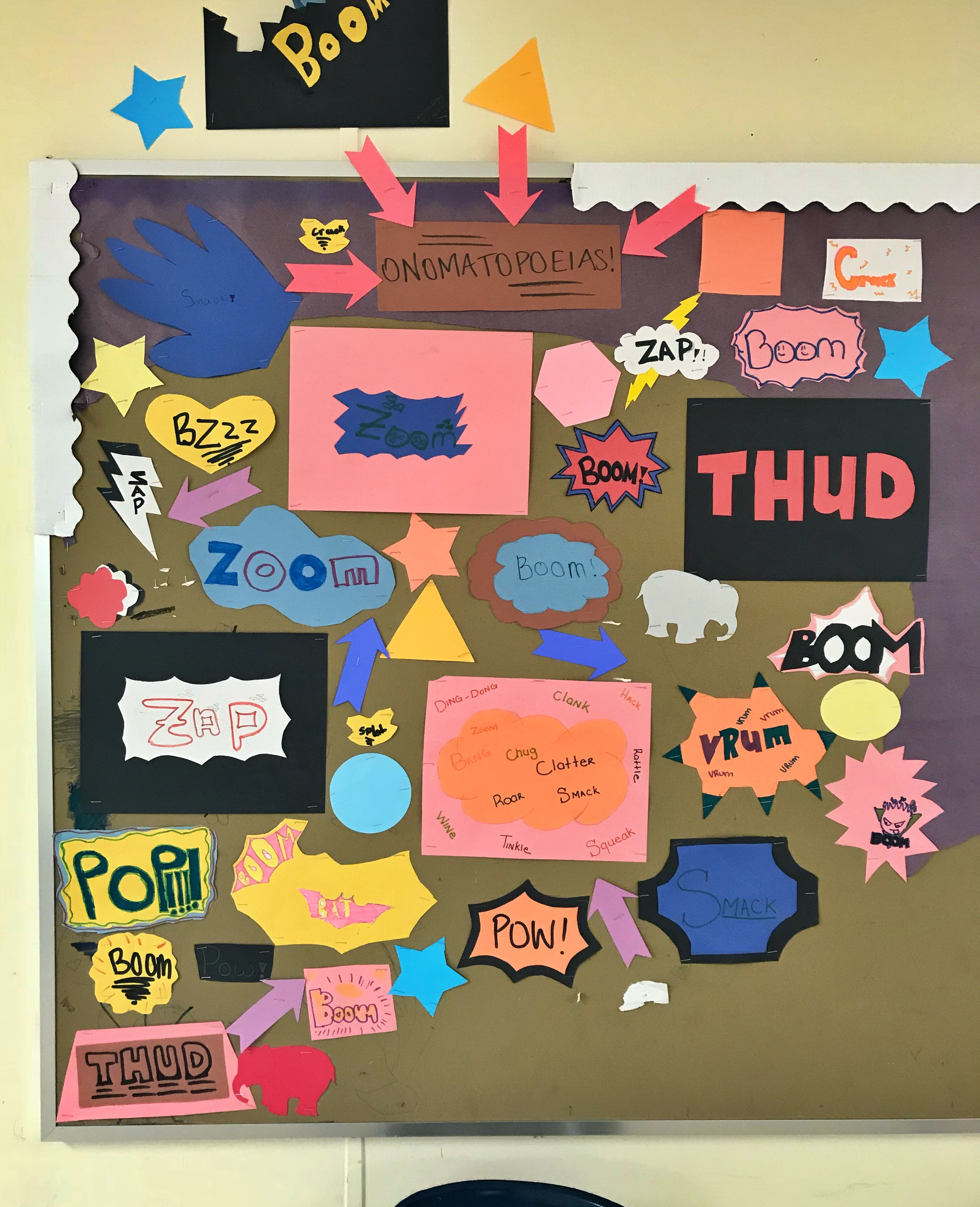 """A classroom pinboard. There is some coloured paper backing and border, but most has been torn away. The board is covered in colourful paper shapes with words like """"boom"""", """"zap"""", """"pop"""" and """"thud"""" written on them."""