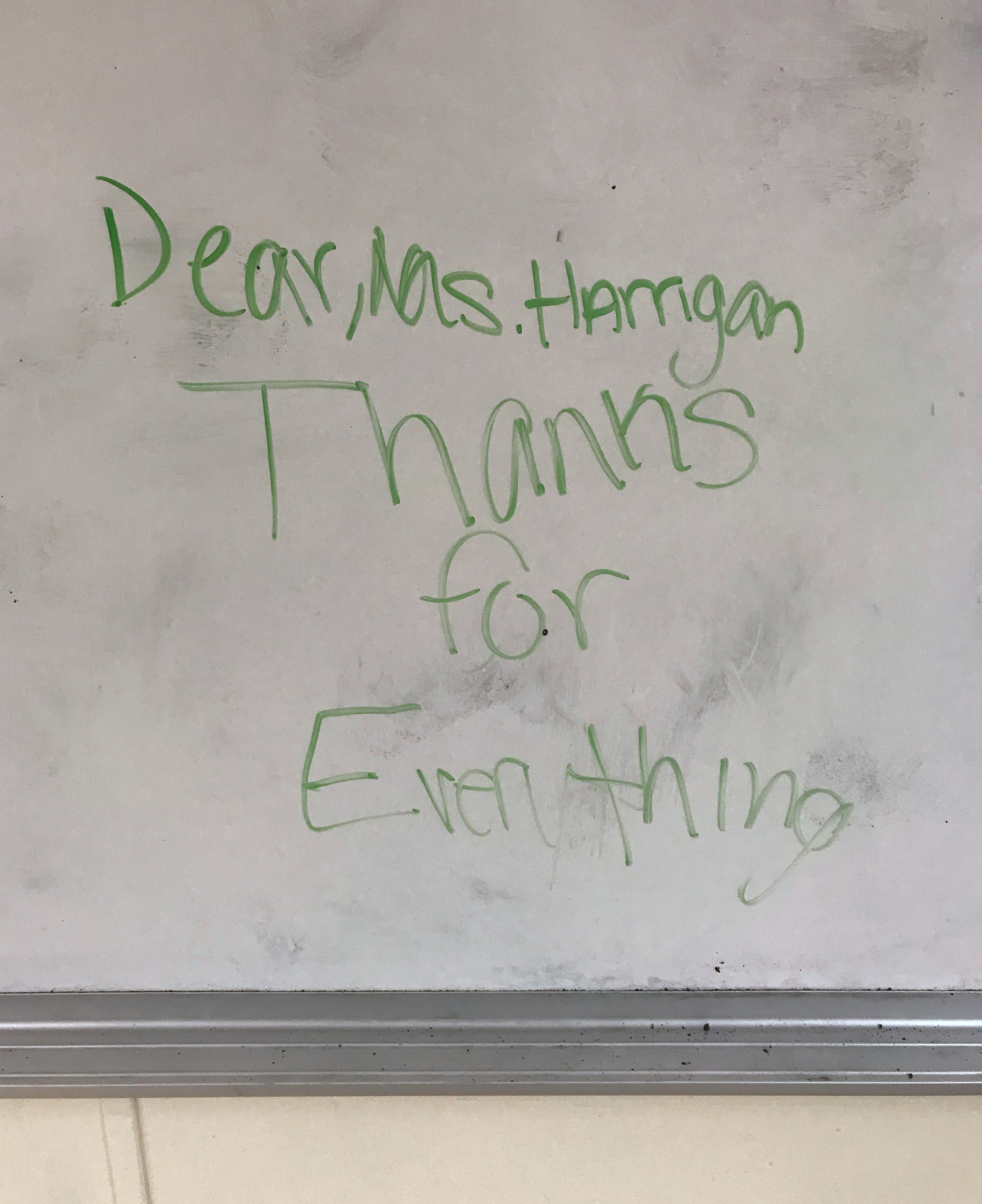 """Writing on a very smudged whiteboard. It says""""Dear, Ms. Harrigan Thanks for Everything""""."""