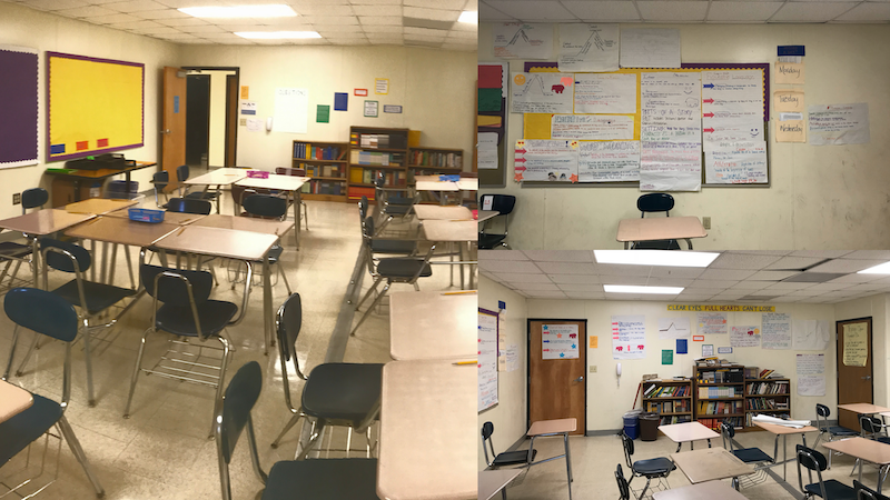 An empty classroom. Desks and chairs are set up in rows. The wall is covered in hand drawn posters. A set of cluttered bookshelves are against the wall, with piles of books on top of them.