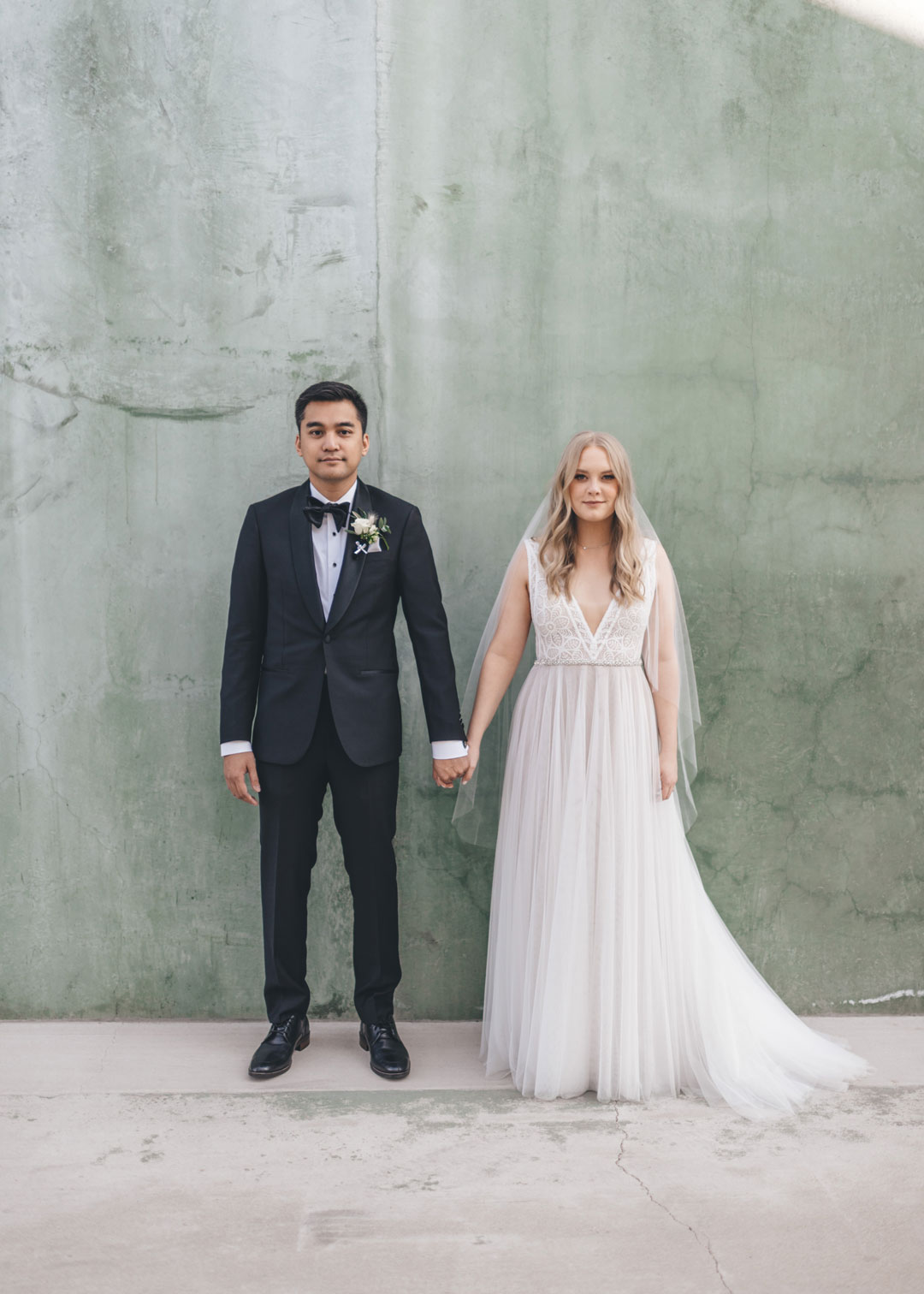groom in black tux standing next to his bride in white tulle wedding dress