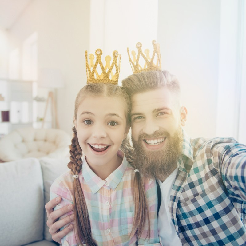 Father and child taking a selfie in crowns