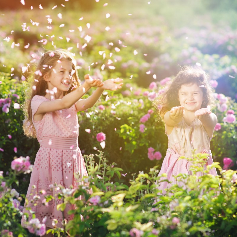 Two children playing in a flower field