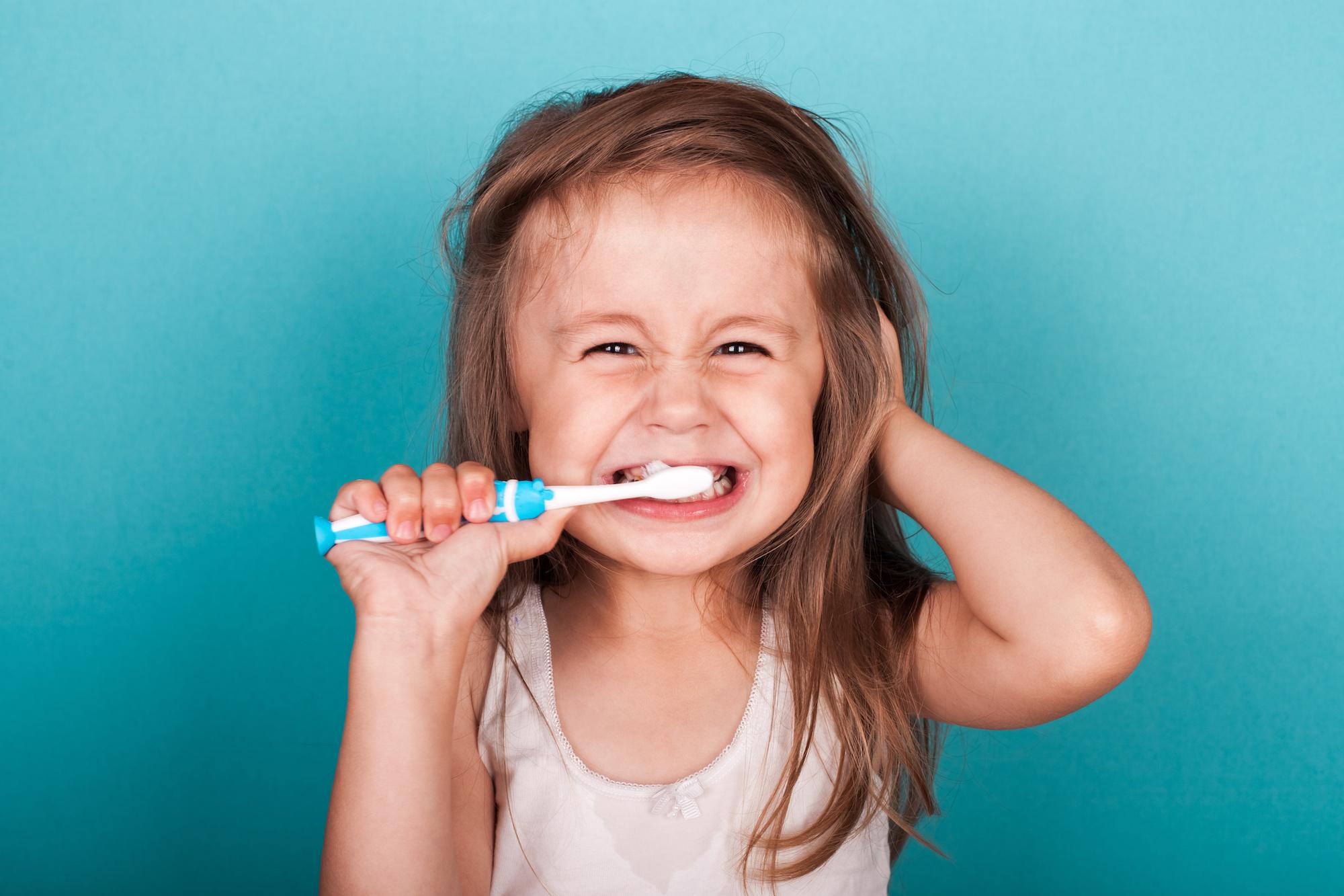 Cute little girl brushing her teeth