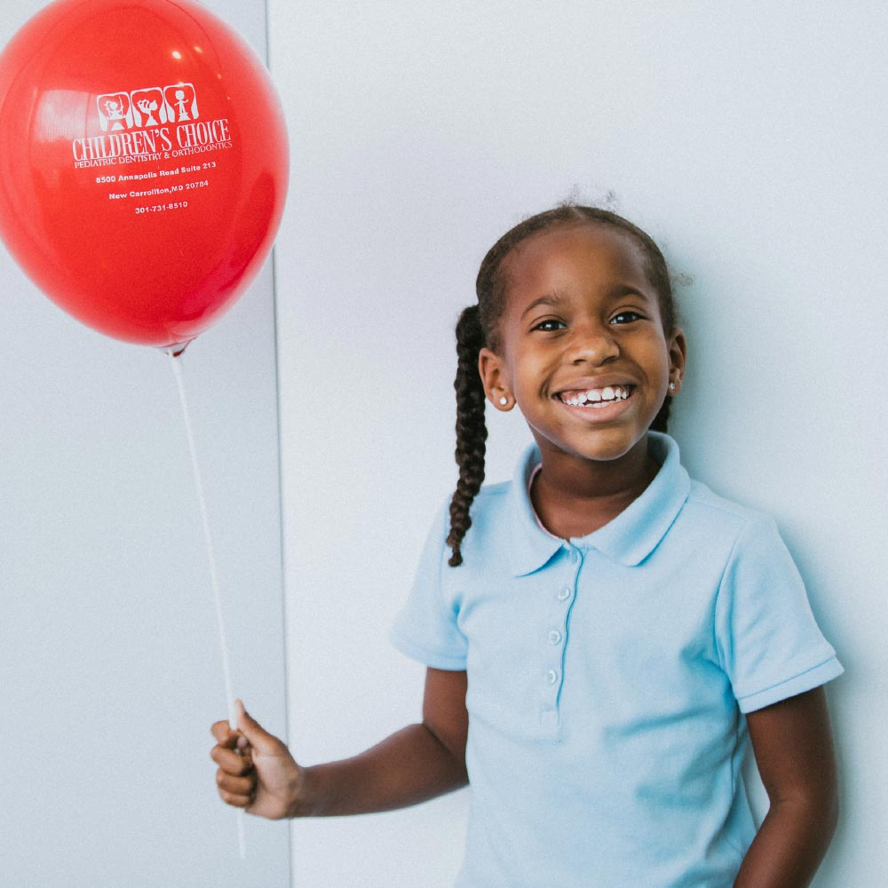 Photo of a young patient holding a balloon
