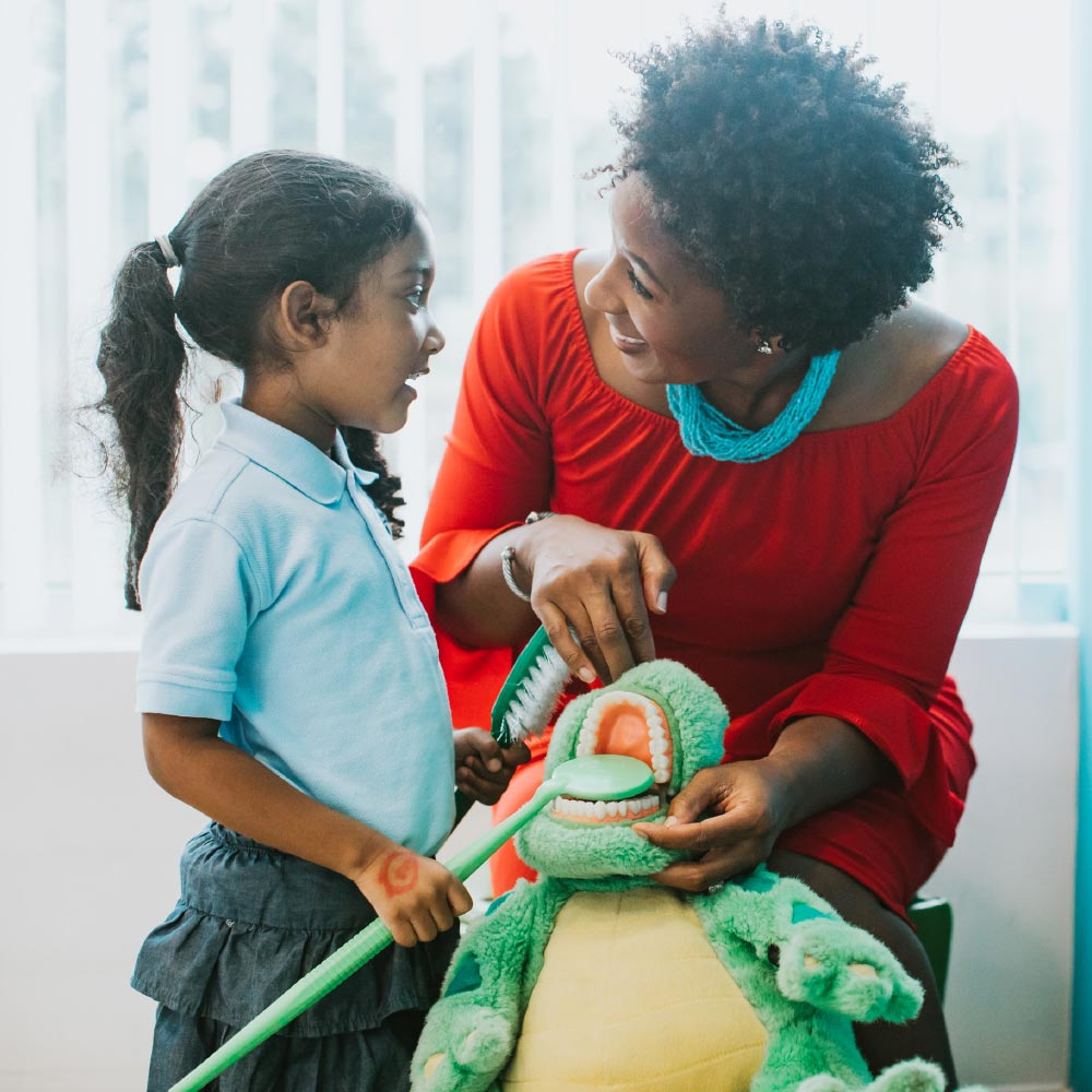 Photo of Dr. Anamelechi talking with a young patient who is brushing a toy dinosaur's teeth
