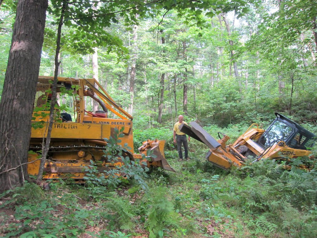 bulldozer pulls the skidsteer back onto the trail