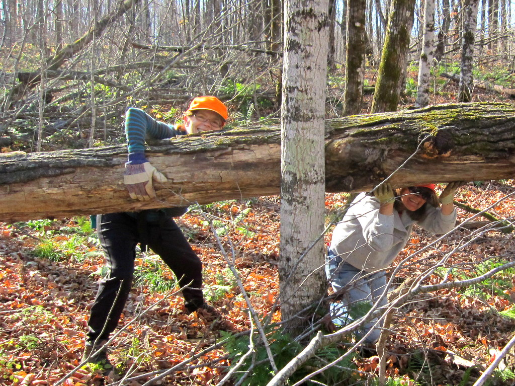 lady volunteers lift a heavy load at the Blue Hills Trail
