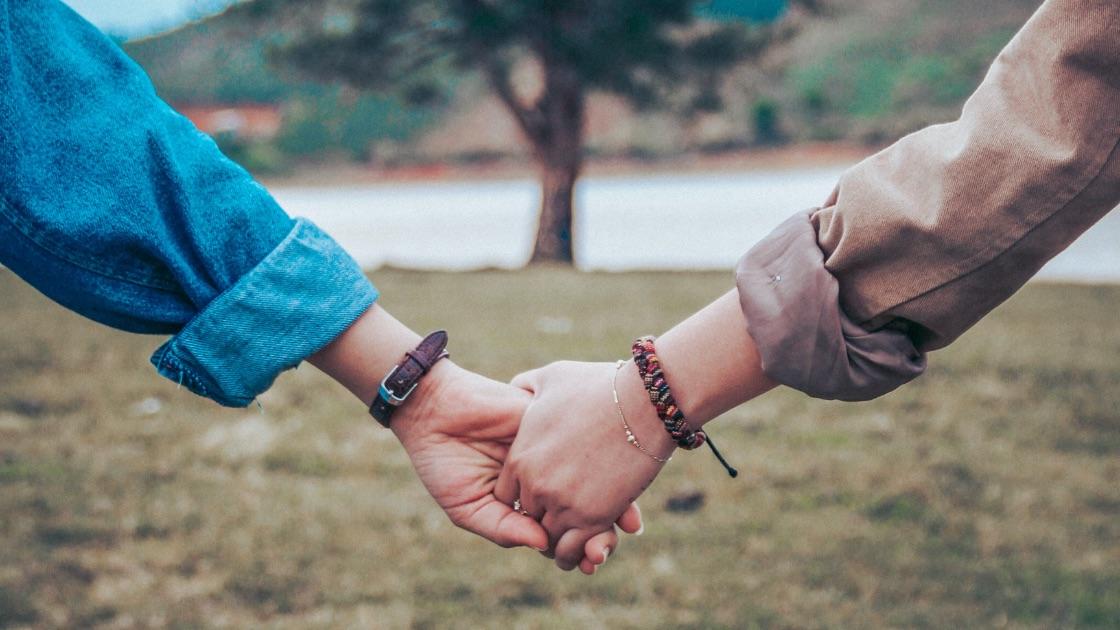 Et kjærestepar som holder hender. Photo: Unsplash