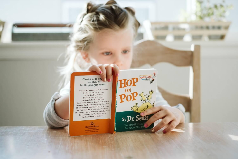 little blonde girl reading hop on pop by dr seuss