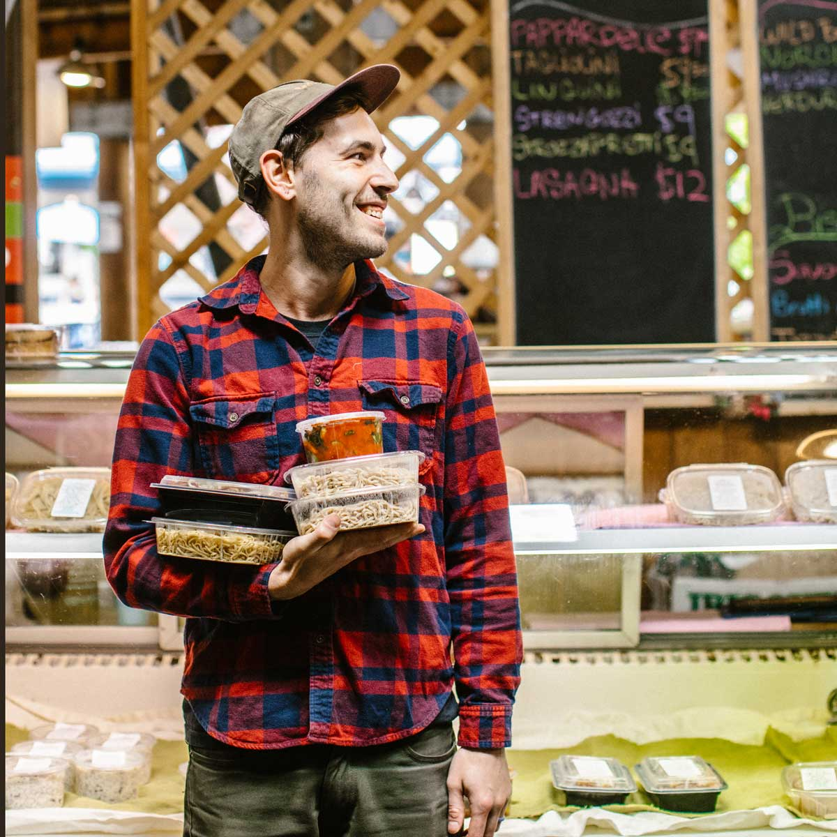 Person in flannel and hat holding italian groceries