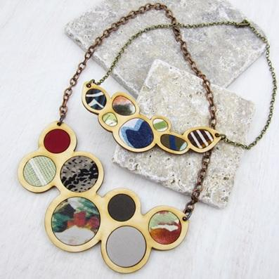 Completed wood necklace with various colors of fabric in-layed into wood.