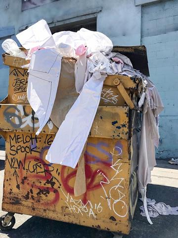 Yellow dumpster with graffiti on the side. Overflowing with fabric and paper patterns