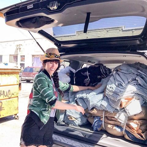 Alyssa standing by the trunk of her car which is packed full of bundles of fabric from L.A. clothing manufacturer