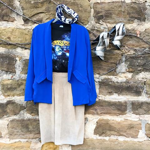 Flat lay: cobalt blue blazer, galaxy graphic tee, high waisted, suede, light beige skirt, criss-cross metallic, chunk heels, and blue and white Regenerous Designs headband