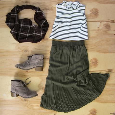 Flat lay: Forest green pleated maxi skirt, black and white plaid crop top, sand colored lace up booties, and Regenerous Designs brown plaid infinity scarf.
