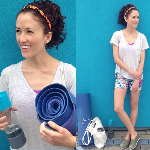 Yoga girl posing with her yoga matt and glass water bottle. She's wearing TOMs slip on shoes, colorful spandex shorts, light grey t-shirt, neon orange Regenerous Designs button band headband.