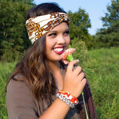 Girl in khaki green top with Regenerous Designs bullet shell bracelets, brown plaid infinity scarf, and orange big braided headband.