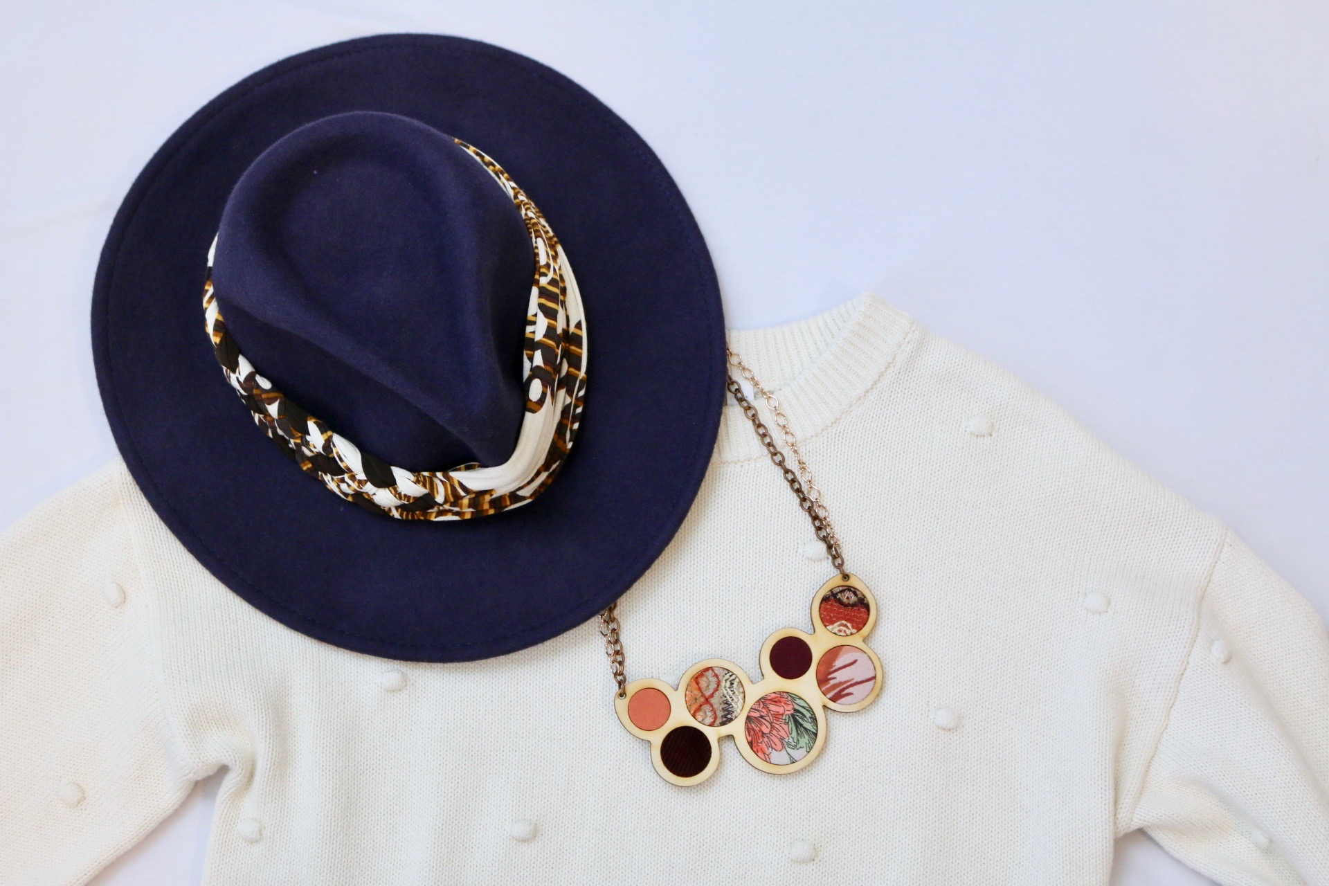 Ivory sweater styled with blue hat with Regenerous Designs Big braided Headband on it. Along with Regenerous Designs Necklace.