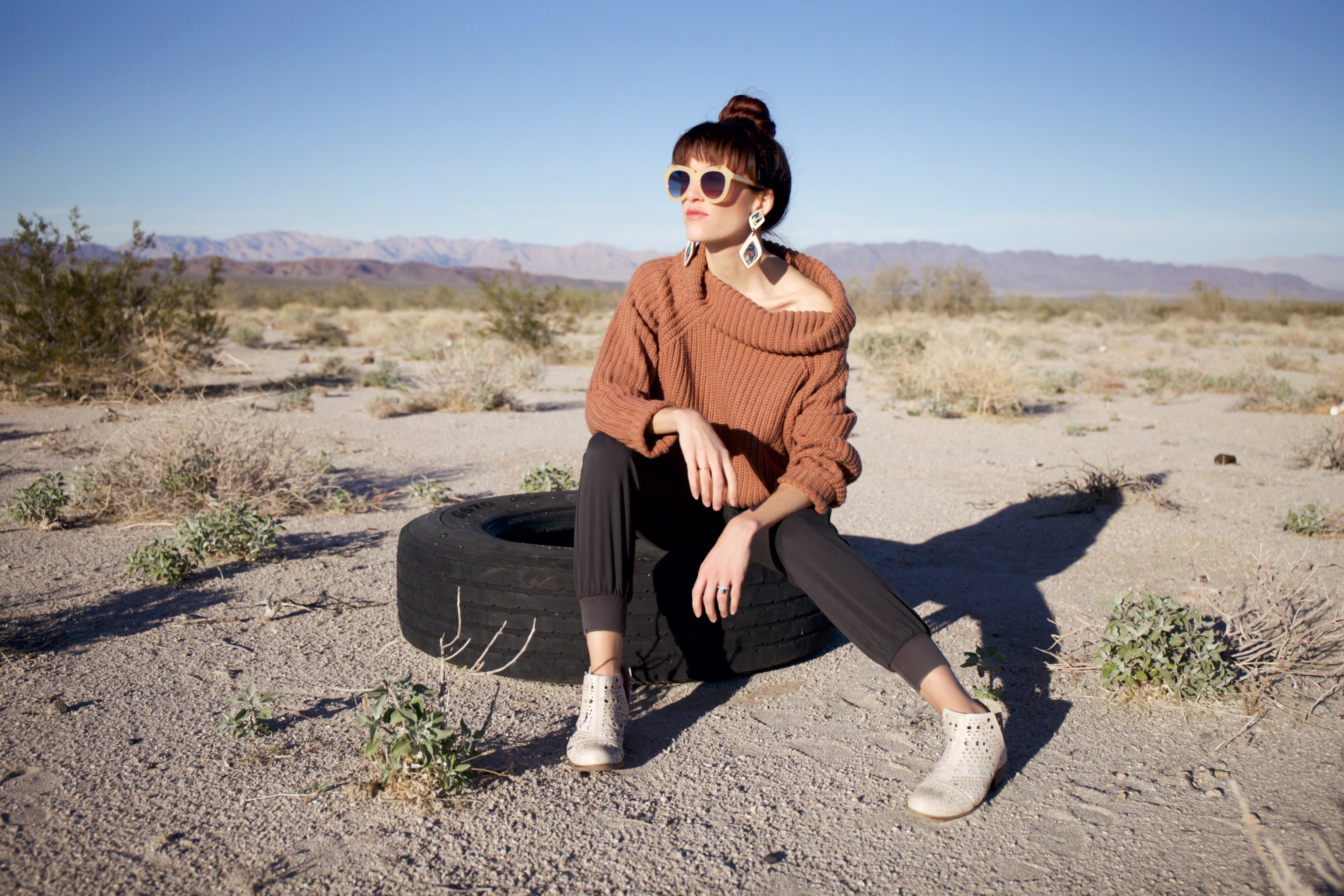Alyssa Bird sitting on an old tire in the desert in Arizona