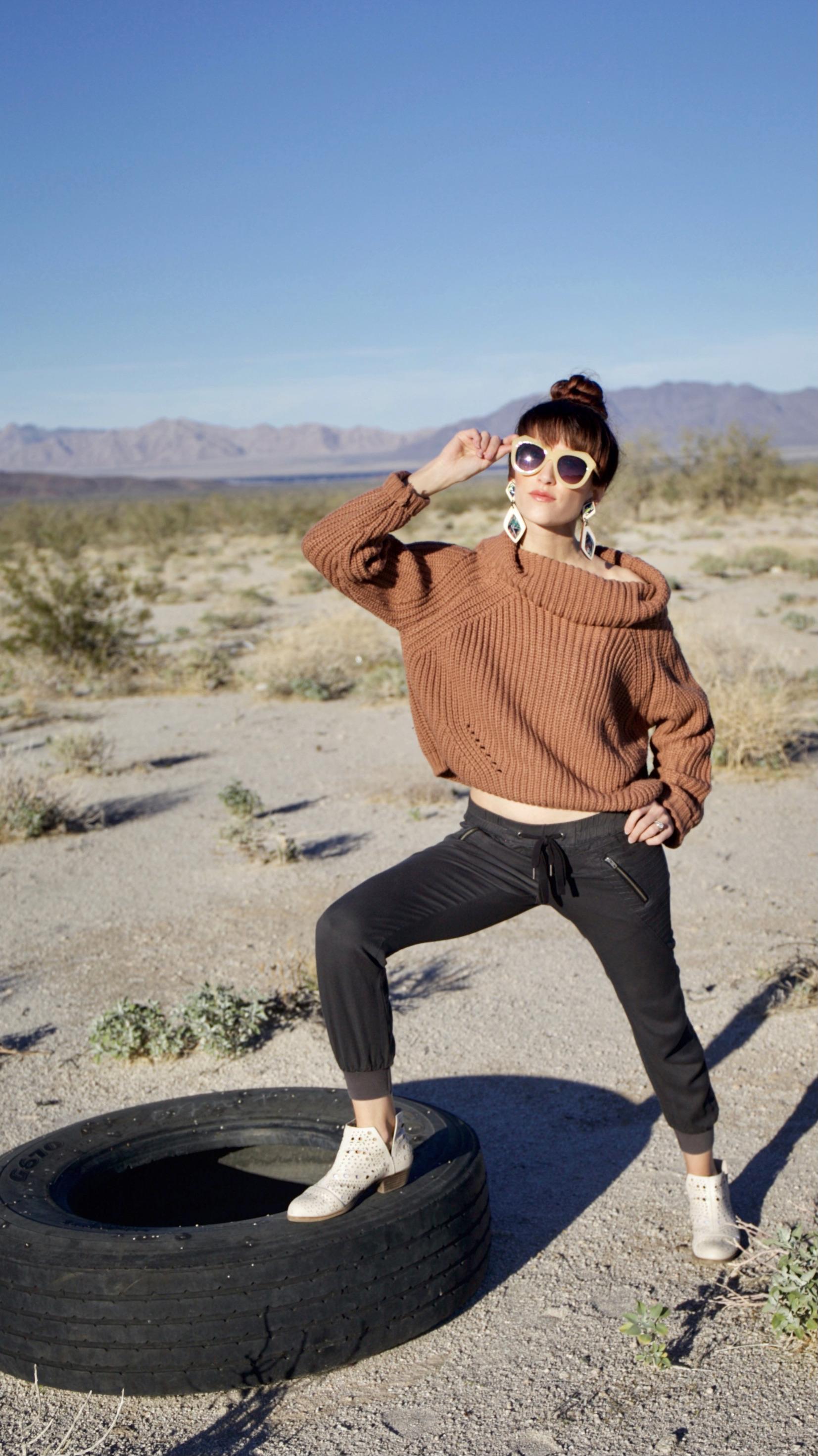 Alyssa Bird standing on an old tire in the desert in Arizona