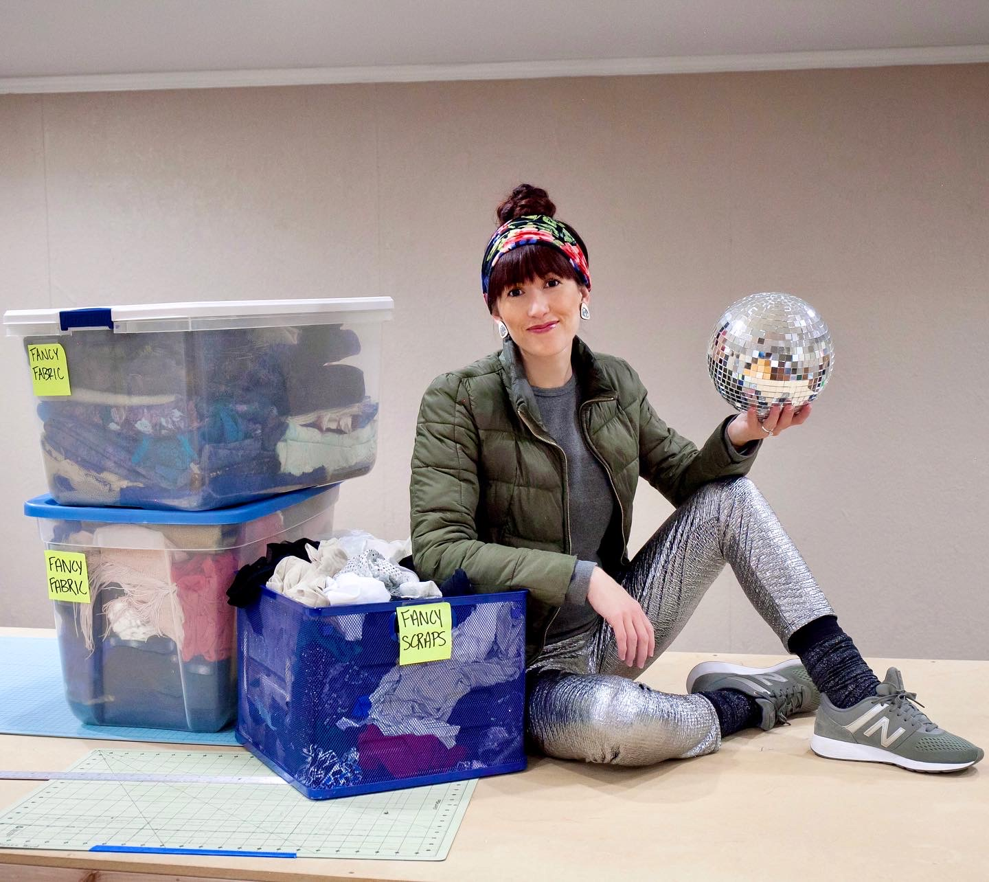 Alyssa Bird wearing Regenerous Designs accessories sitting on a table with boxes of fabric and holding a disco ball