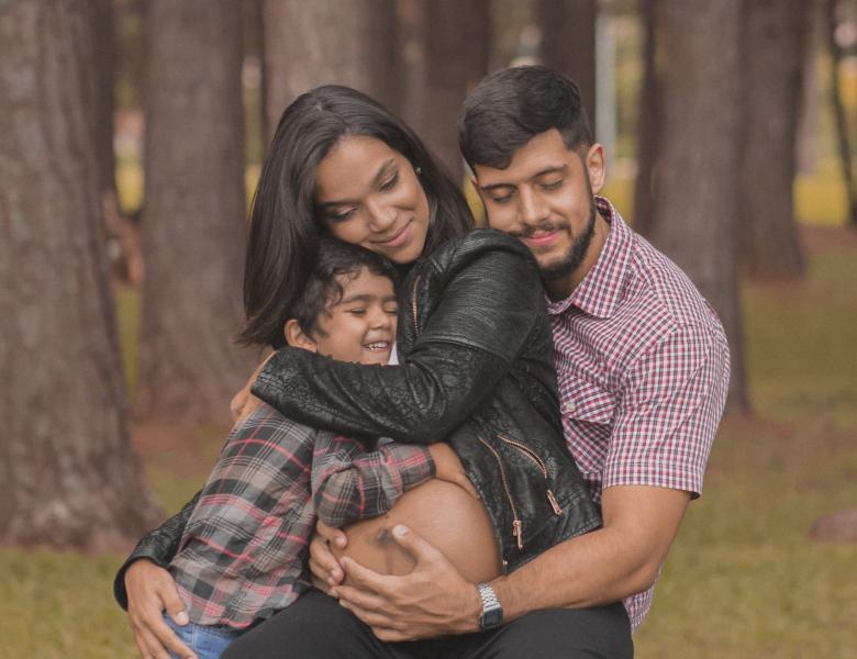Child, woman, man holding pregancy bump