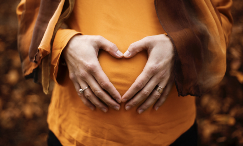 Pregnant women in organge clothes with hands over bump in heart sign