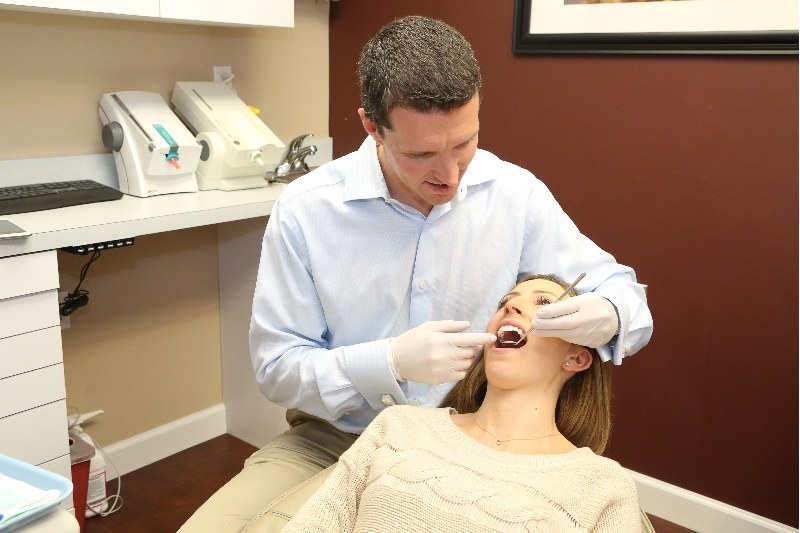 Dr. Cox performing a teeth cleaning on a woman