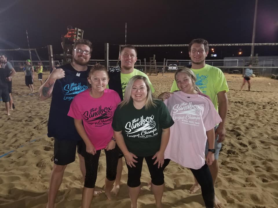 picture of a group of volleyball players wearing the sandbox volleyball logo t-shirts