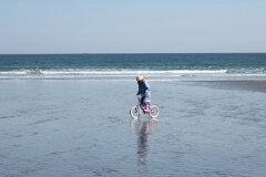 Girl Cycling on the Beach
